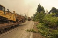 Bulldozers open fire break at a forest during a wildfire near Kechries village on the island of Evia, about 144 kilometers (90 miles) north of Athens, Greece, Thursday, Aug. 5, 2021. Forest fires fueled by a protracted heat wave raged overnight and into Thursday in Greece, threatening the archaeological site at the birthplace of the modern Olympics and forcing the evacuation of dozens of villages. (AP Photo/Thodoris Nikolaou)