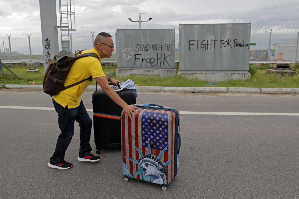 A passenger walks to airport as pro-democracy protestors blocked a road outside the airport in Hong Kong, Sunday, Sept. 1, 2019. Train service to Hong Kong's airport was suspended Sunday as pro-democracy demonstrators gathered there, while protesters outside the British Consulate called on London to grant citizenship to people born in the former colony before its return to China. (AP Photo/Kin Cheung)