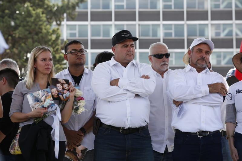 Adriana LeBaron, left, Julian LeBaron, center, and Adrian LeBaron, right, stand during a protest against the first year in office of Mexico's President Andres Manuel Lopez Obrador, in Mexico City, Monday, Dec. 1, 2019. The LeBaron's joined a protest on Reforma avenue to expressed anger and frustration over increasingly appalling incidents of violence, a stagnant economy and deepening political divisions in the country. (AP Photo/Ginnette Riquelme)