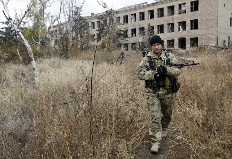 A Ukrainian soldier patrols past a destroyed school in the village of Pisky near Donetsk October 26, 2015 (AFP Photo/Anatolii Stepanov)