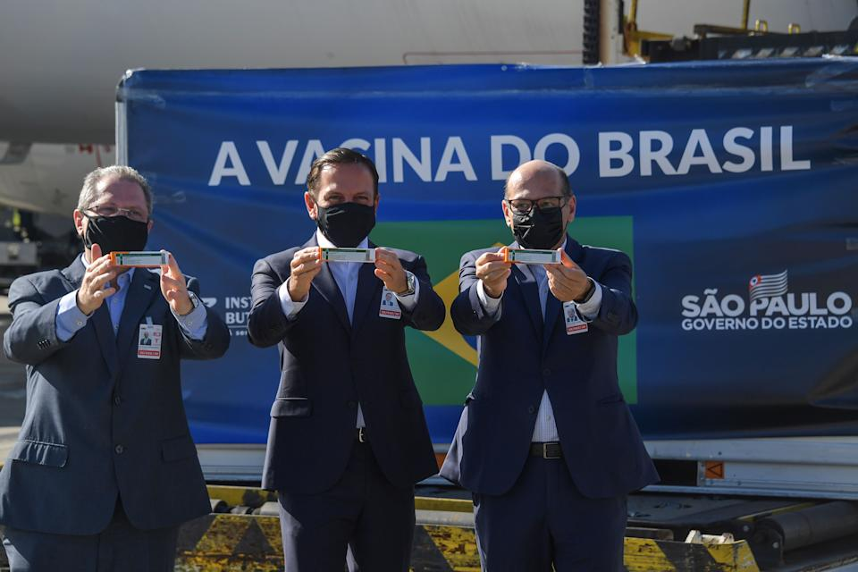 Sao Paulo Governor Joao Doria (C), Sao Paulo state Health Secretary Jean Gorinchteyn (L) and Butantan Institute director Dimas Covas (R), pose for photos holding doses of the CoronaVac vaccine against COVID-19 next to a container unloaded from a cargo plane that arrived from China at Guarulhos International Airport in Guarulhos, Sao Paulo state, Brazil, on December 18, 2020. - Brazil received Friday the third lot with 1,900,000 doses of the CoronaVac vaccine, developed by the Chinese laboratory Sinovac Biotech. (Photo by NELSON ALMEIDA / AFP) (Photo by NELSON ALMEIDA/AFP via Getty Images)
