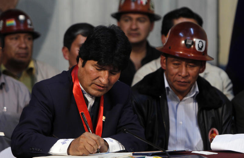 Bolivia's President Evo Morales, left, signs the new retirement law in La Paz, Bolivia, Friday, Dec. 10, 2010. The law lowers the country's retirement age to 58 and also nationalizes the pension system and extends coverage to the 60 percent of Bolivians who work in the informal economy, as long as they make contributions. At right is Pedro Montes, leader of Bolivia's Workers Central Union. (AP Photo/Juan Karita)