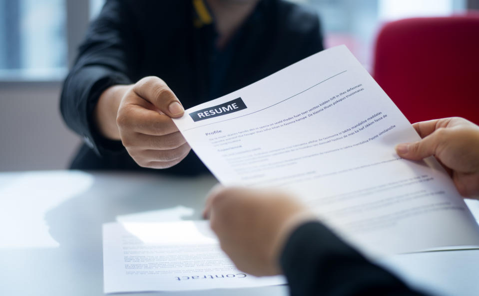 Person handing resume to another person at office desk.