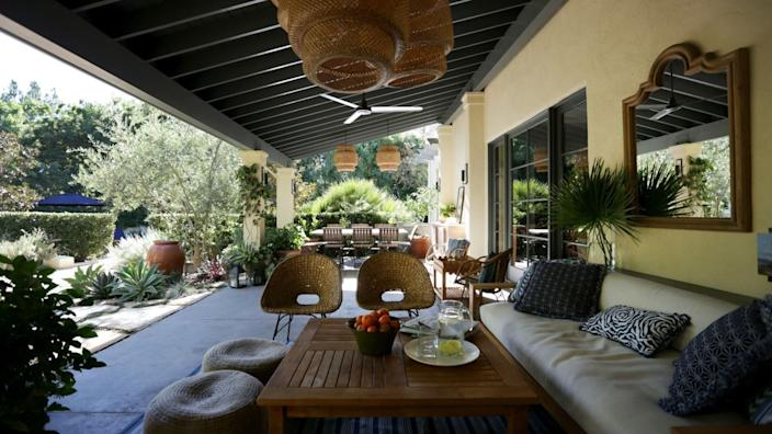 "Rattan chairs and woven ottomans provide multiple seating options in this Bel-Air garden. <span class=""copyright"">(Katie Falkenberg / Los Angeles Times)</span>"