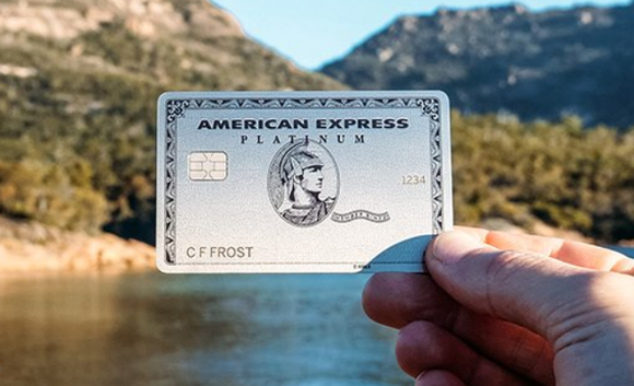 A person holding an American Express credit card with a lake in the background.