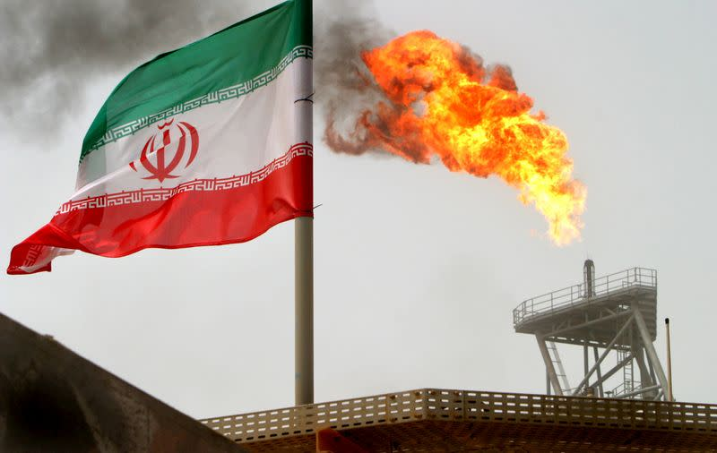 A gas flare on an oil production platform is seen alongside an Iranian flag in the Gulf
