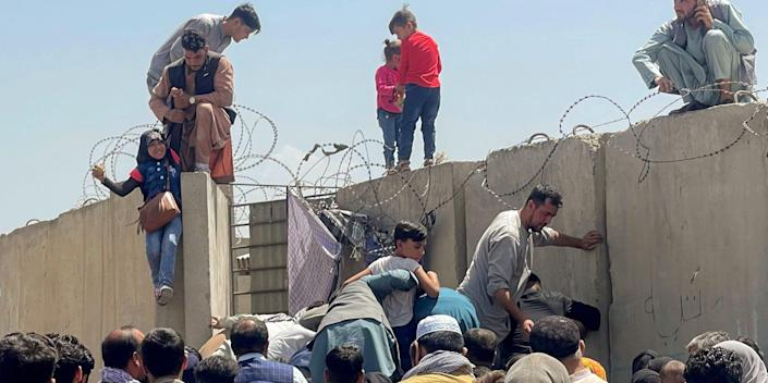 Afghanis climbing over the Kabul Airport fence in Afghanistan