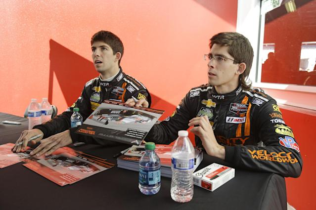 Drivers Ricky Taylor, left, and Jordan Taylor talk with fans during an autograph session prior to the start of the IMSA Series Rolex 24 hour auto race at Daytona International Speedway in Daytona Beach, Fla., Saturday, Jan. 25, 2014.(AP Photo/John Raoux)