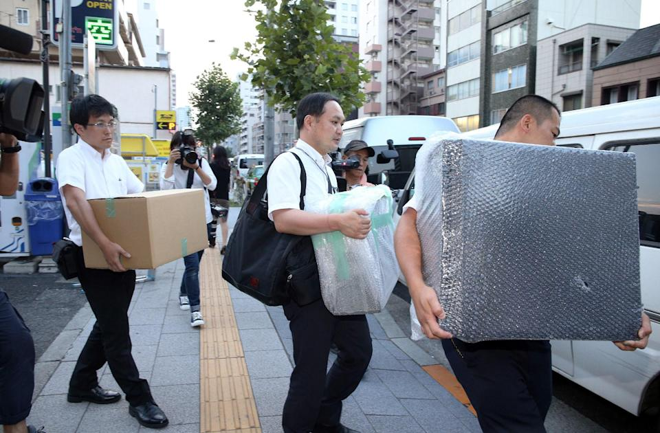 Police officers carry pieces of evidence out of house of Mark Karpeles, the head of defunct Bitcoin exchange MtGox, in Tokyo on August 3, 2015. (Photo: JIJI PRESS/AFP/Getty Images)