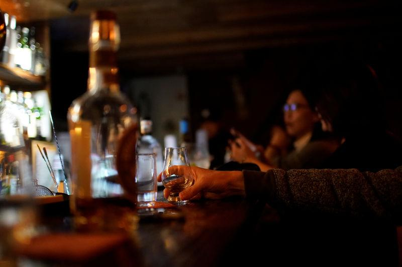 A man drinks American whiskey at a bar in Shanghai