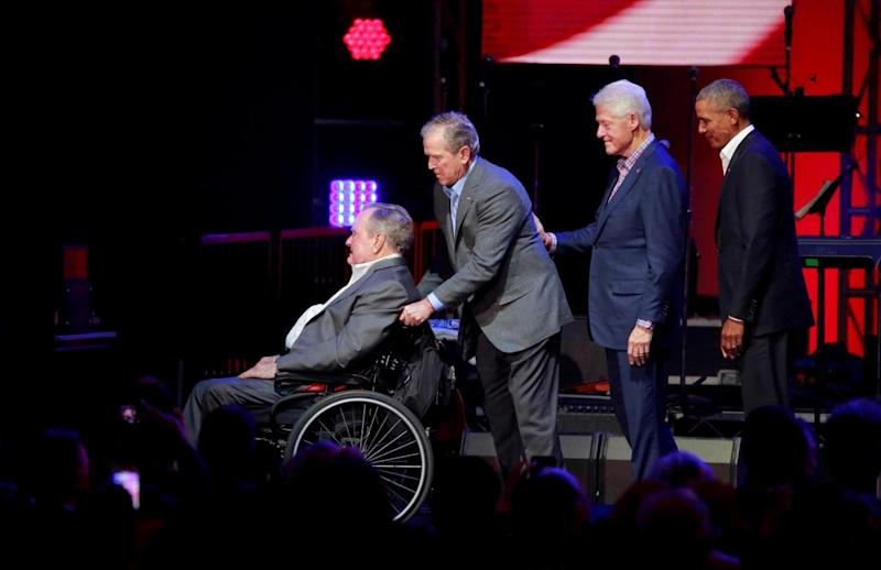 Former US President George H.W. Bush is helped off the stage by George W. Bush as Bill Clinton and Barack Obama follow close behind (REUTERS)