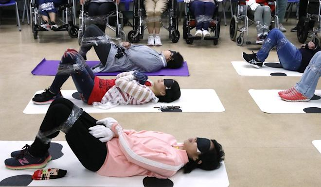 Carers are tied up and blindfolded during a demonstration led by the Christian Family Service Centre, a local NGO. Photo: K. Y. Cheng