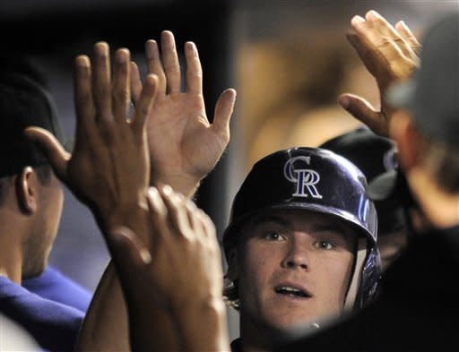 Colorado Rockies' Josh Rutledge high-fives teammates after scoring against the Miami Marlins during the fifth inning of a baseball game in Denver, Friday, Aug. 17, 2012. (AP Photo/Jack Dempsey)
