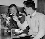 <p>A young couple, presumably on a date by the looks of things, enjoy a conversation over two large frozen treats.</p>
