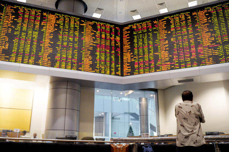A visitor stands in front of private stock trading boards at a private stock market gallery in Kuala Lumpur, Malaysia, Friday, Dec. 7, 2018. Asian shares were mostly higher Friday after gains on Wall Street but investors continued to watch for news about U.S.-China trade friction. (AP Photo/Yam G-Jun)