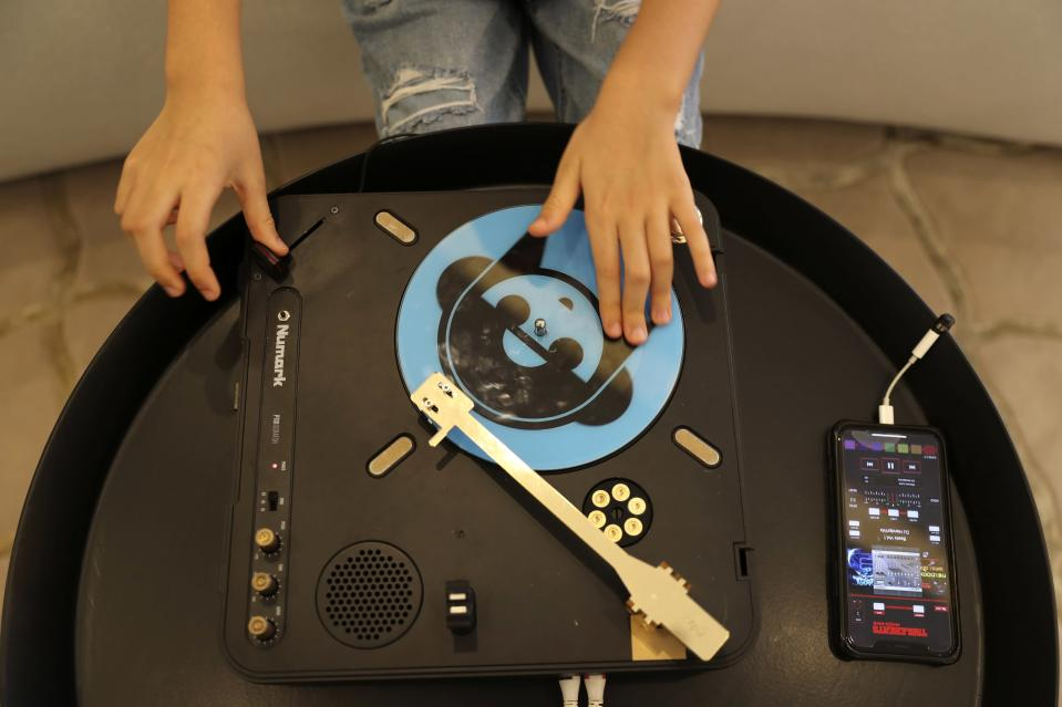 Michelle Rasul enjoys scratching her turntable in the lobby of her apartment building in Dubai, United Arab Emirates, Sunday, May 9, 2021. Rasul, a 9-year-old girl from Azerbaijan who lives in Dubai, is scratching her way to the top as a DJ after competing in the DMC World DJ Championship. (AP Photo/Kamran Jebreili)