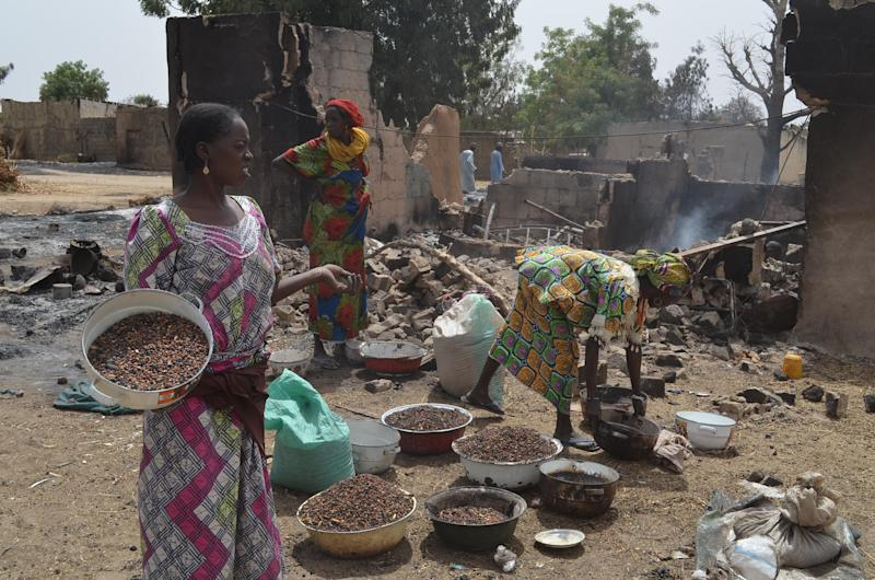 Women gather cooking ingredients in front of a burnt-out house in Mainok, outside Maiduguri, on March 6, 2014 (AFP Photo/)