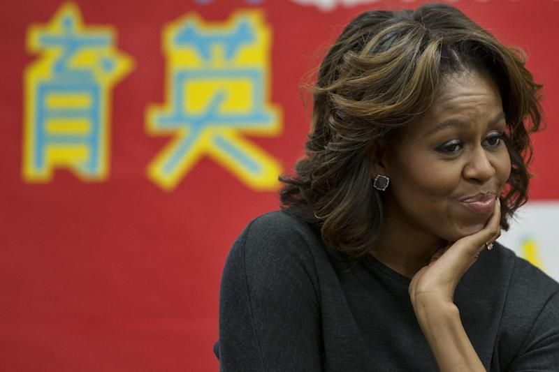 First lady Michelle Obama listens as a 6th grade class talks about a class trip they took to China, Tuesday, March 4, 2014, at Washington Yu Ying Public Charter School in Washington. The first lady is expected to take a trip to China along with her daughters and mother in March. (AP Photo/Jacquelyn Martin)