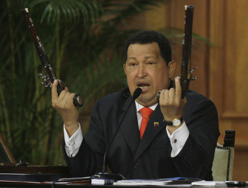 Venezuela's President Hugo Chavez holds up a pair of pistols that he says belonged to Venezuela's independence hero Simon Bolivar during a ceremony marking 229th anniversary of Bolivar's birth at Miraflores presidential palace in Caracas, Venezuela, Tuesday, July 24, 2012. Bolivar is the namesake of Chavez's Bolivarian Revolution movement, and his government is putting the finishing touches on a new mausoleum to house Bolivar's remains. (AP Photo/Fernando Llano)