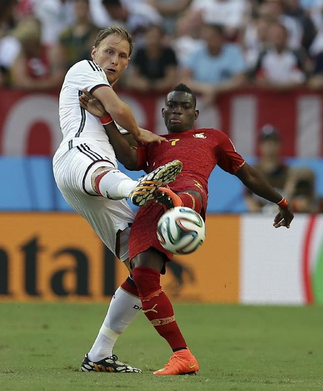 Germany's Benedikt Hoewedes, left, and Ghana's Christian Atsu reach out to kick the ball during the group G World Cup soccer match between Germany and Ghana at the Arena Castelao in Fortaleza, Brazil, Saturday, June 21, 2014. (AP Photo/Martin Mejia)