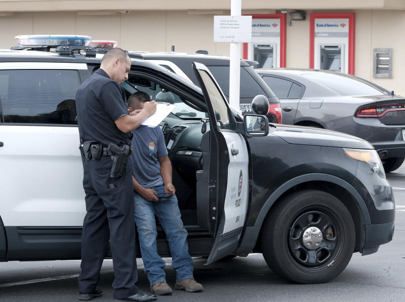 A LAPD officer talks to the victim of an attempted robbery in Los Angeles on Thursday, July 25, 2019. A gunman shot five people, killing three, in two attacks early Thursday in Los Angeles that police say took the lives of two of his family members and an acquaintance. A manhunt was underway for Gerry Dean Zarragoza, 26, who may be driving a blue Jeep Liberty with paper license plates, police spokesman Officer Drake Madison said. (David Crane/The Orange County Register via AP)