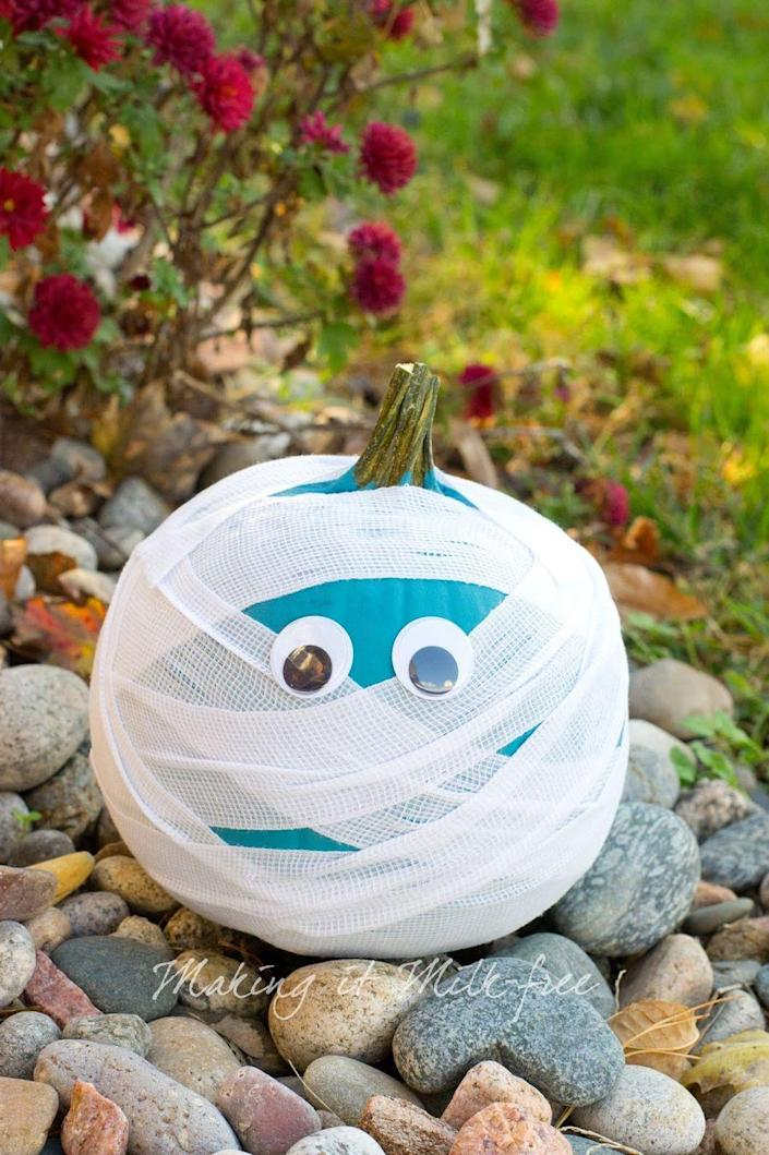 """<p>Use a bright color, like teal, to make this mummy pumpkin stand out. </p><p><strong><em>Get the tutorial from <a href=""""http://www.makingitmilkfree.com/2015/10/keep-it-teal-teal-pumpkin-project.html"""" rel=""""nofollow noopener"""" target=""""_blank"""" data-ylk=""""slk:Making It Milk-Free"""" class=""""link rapid-noclick-resp"""">Making It Milk-Free</a>.</em> </strong></p>"""