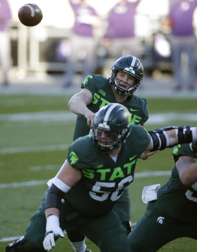 Michigan State quarterback Rocky Lombardi, top, throws a pass as guard Matt Carrick blocks against Northwestern during the first quarter of an NCAA college football game, Saturday, Nov. 28, 2020, in East Lansing, Mich. (AP Photo/Al Goldis)