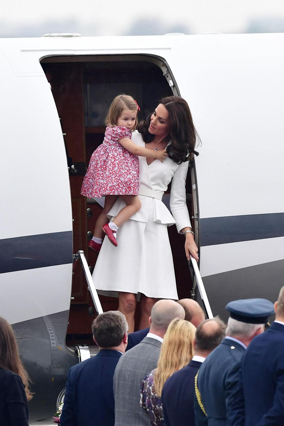 <p><b><b><b>The Duchess of Cambridge left the plane holding Princess Charlotte. The former wore a white Alexander McQueen peplum dress while Princess Charlotte looked adorable in a red, floral dress. Together, the duo made up the colours of the Polish flag. Diplomatic dressing if we ever saw it. <em>[Photo: PA]</em> </b></b></b></p>