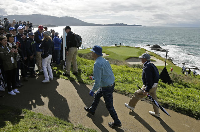 Bill Murray, center, walks up to the gallery to hand out strawberries on the seventh hole of the Pebble Beach Golf Links during the third round of the AT&T Pebble Beach Pro-Am golf tournament Saturday, Feb. 9, 2019, in Pebble Beach, Calif. (AP Photo/Eric Risberg)