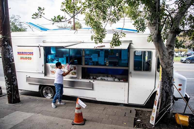 A lone customer gets his order at the Mariscos Jaliscos truck.