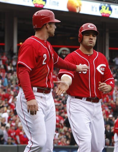 Cincinnati Reds' Zack Cozart (2) congratulates teammate Joey Votto (19) at home plate after they scored on a Jay Bruce double hit off Houston Astros starting pitcher Lucas Harrell during the third inning of a baseball game on Saturday, April 28, 2012, in Cincinnati. (AP Photo/David Kohl)