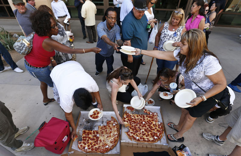 Several of the dozens of spectators in front of Maricopa County Superior Court building share pizza delivered to the crowd as they wait for a verdict in the Jodi Arias murder trial, Tuesday, May 7, 2013, in Phoenix. A Phoenix jury is on its third day of deliberations in the trial of Jodi Arias, who is accused of murdering her one-time boyfriend, Travis Alexander, in Arizona. (AP Photo/Ross D. Franklin)