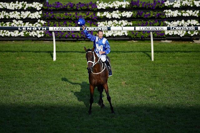 Jockey Hugh Bowman celebrates with Winx after the mare's final race (AFP Photo/Wendell TEODORO)