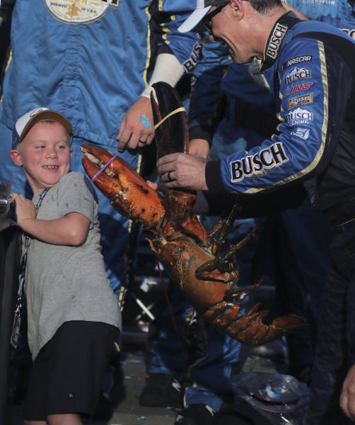 Kevin Harvick holds a giant lobster as he jokes with his son Keelan after winning a NASCAR Cup Series auto race at New Hampshire Motor Speedway in Loudon, N.H., Sunday, July 21, 2019. (AP Photo/Charles Krupa)