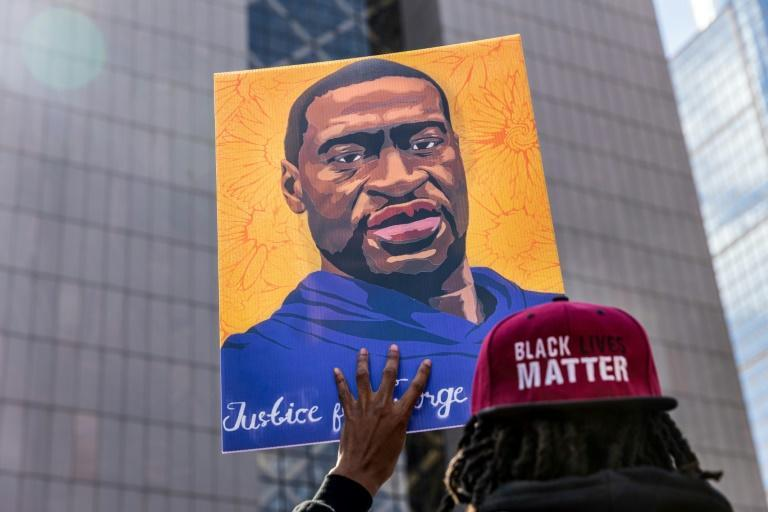 A demonstrator holds a sign with a picture of George Floyd during a protest outside the Hennepin County Government Center in Minneapolis, Minnesota, where former police officer Derek Chauvin is on trial