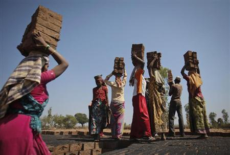 Labourers carry bricks to be baked in kiln at brickyard on outskirts of Karad in Satara district