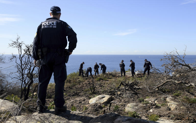Police search a headland in Sydney, Tuesday, May 12, 2020, following an arrest in relation to the death of a man in 1998. More than 30 years after American mathematician Scott Johnson died after falling off a cliff in Sydney, a man has been charged with his death in an apparent gay hate crime that police believe was one of many over several decades in Australia's largest city. (AAP Image/Dan Himbrechts)
