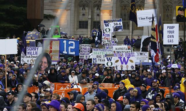 Washington fans hold signs during the broadest of ESPN College GameDay Saturday, Oct. 12, 2013, on the University of Washington campus before an NCAA college football game between Washington and Oregon in Seattle. (AP Photo/Ted S. Warren)