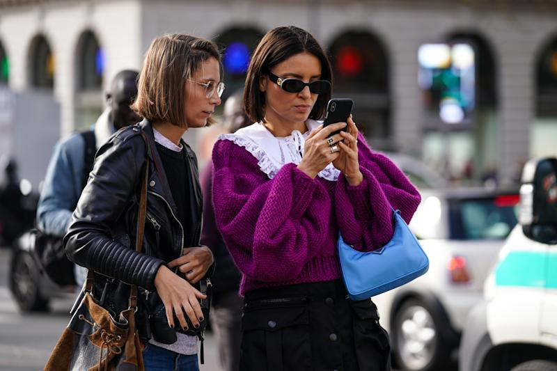 PARIS, FRANCE - SEPTEMBER 30: A guest (L) wears a black leather jacket ; a guest (R) wears a purple oversized wool pullover with a white lace collar, a blue Prada bag, outside Stella McCartney, during Paris Fashion Week - Womenswear Spring Summer 2020, on September 30, 2019 in Paris, France. (Photo by Edward Berthelot/Getty Images)