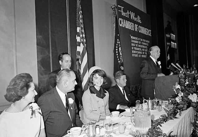 <p>First lady Jacqueline Kennedy is all smiles as she attends a breakfast held by the Chamber of Commerce in Fort Worth, Tex., Nov. 22, 1963. Seated at the dais from left are, Lady Bird Johnson, Vice President Lyndon B. Johnson, Mrs. Kennedy and President John F. Kennedy. Man at podium is unidentified. (Photo: Ferd Kaufman/AP) </p>