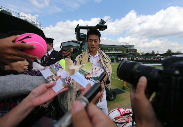 Japan's Kei Nishikori signs autographs after winning his men's singles third round match against Italy's Simon Bolelli at the 2014 Wimbledon Championships in Wimbledon, southwest London, on June 30, 2014 (AFP Photo/Andrew Cowie)