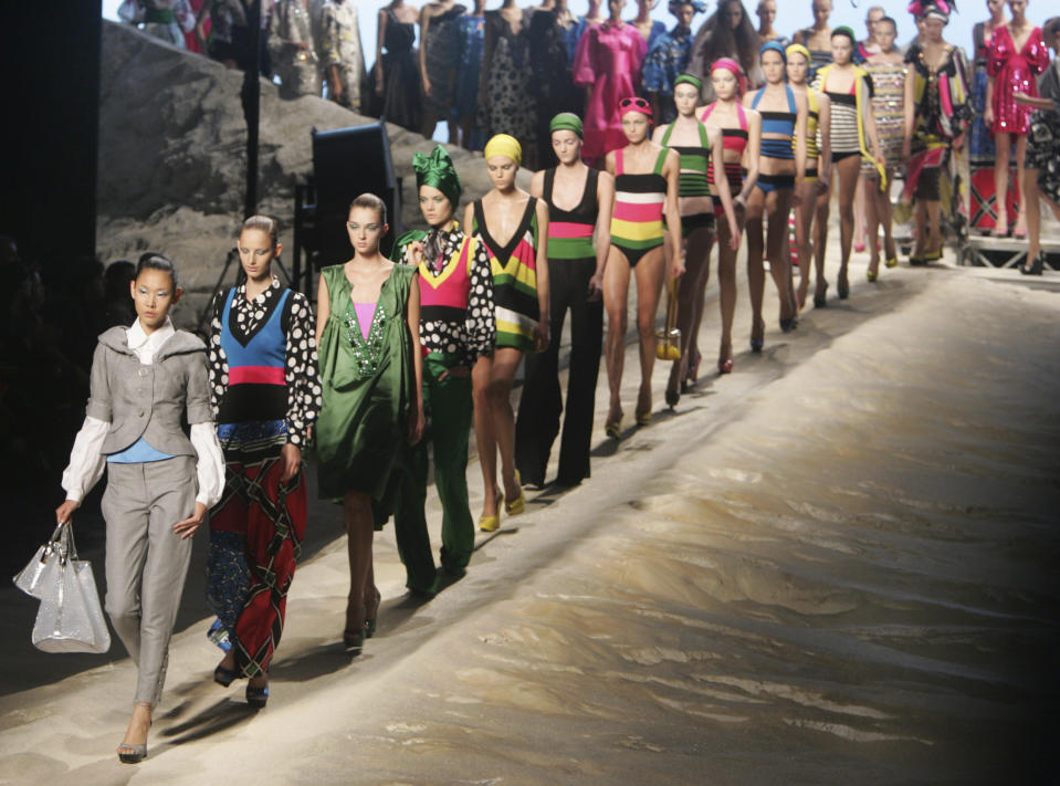 FILE - In this Saturday Oct. 7, 2006 file photo, models take the runway at the end of the presentation of the Spring-Summer 2007 ready to wear collection by by Italian fashion designer Antonio Marras for Kenzo, in Paris. Fashion designer Kenzo Takada dies from COVID-19 complications at age 81 near Paris, spokeswoman and reports said Sunday Oct. 4, 2020. (AP Photo/Remy de la Mauviniere, file)