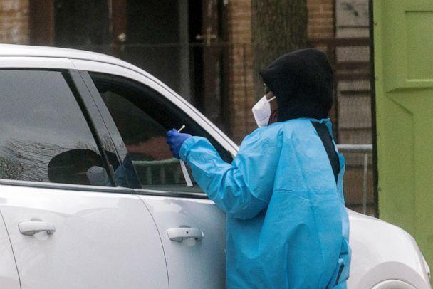 PHOTO: A health worker does a coronavirus disease (COVID-19) test as people wait at a drive-through COVID-19 testing center in a local street, in Newark, New Jersey, April 2, 2021. (Eduardo Munoz/Reuters)