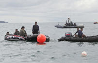 Indonesian Navy divers position their boats near marker buoys as they continue the search for the wreckage of the crashed Sriwijaya Air passenger jet continues in the Java Sea, near Jakarta, Indonesia, Tuesday, Jan. 12, 2021. Indonesian navy divers were searching through plane debris and seabed mud Tuesday looking for the black boxes of a Sriwijaya Air jet that nosedived into the Java Sea over the weekend with 62 people aboard. (AP Photo/Tatan Syuflana)
