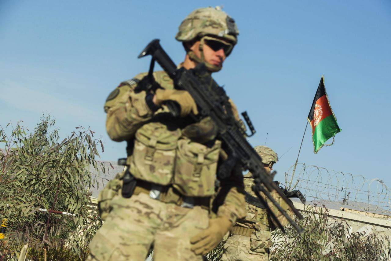 A U.S. soldier from Dragon Company of the 3rd Cavalry Regiment stands in front of an Afghan flag during a mission near forward operating base Gamberi in the Laghman province of Afghanistan December 28, 2014. REUTERS/Lucas Jackson (AFGHANISTAN - Tags: CIVIL UNREST POLITICS MILITARY)