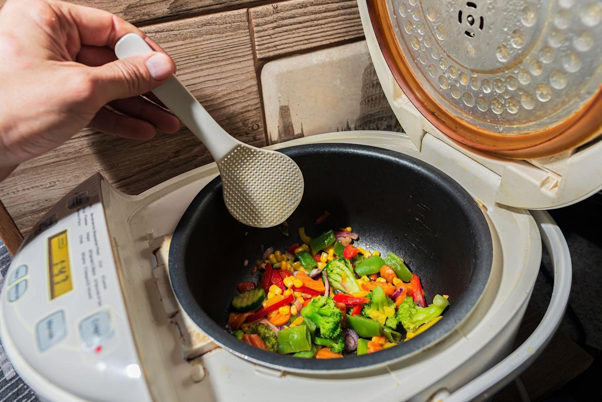 mixed set of different vegetarian vegetables in a white multicooker is stirred with a kitchen plastic Scraper. Onions, peppers, paprika, peas, corn, broccoli, cabbage and cucumber