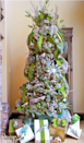 """<p>Going vertical, use the same green patterned ribbon throughout your tree as you do on the presents that sit underneath the tree. </p><p><em><a href=""""http://www.designdazzle.com/2013/11/michaels-dream-tree-challenge-2013/?crlt.pid=camp.fgzkAxWpX0o0"""" rel=""""nofollow noopener"""" target=""""_blank"""" data-ylk=""""slk:Get the tutorial at Design Dazzle »"""" class=""""link rapid-noclick-resp"""">Get the tutorial at Design Dazzle »</a></em></p>"""