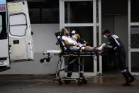 Healthcare workers receive a patient suspected of having COVID-19 at the public HRAN Hospital in Brasilia, Brazil, Monday, March 8, 2021. (AP Photo/Eraldo Peres)