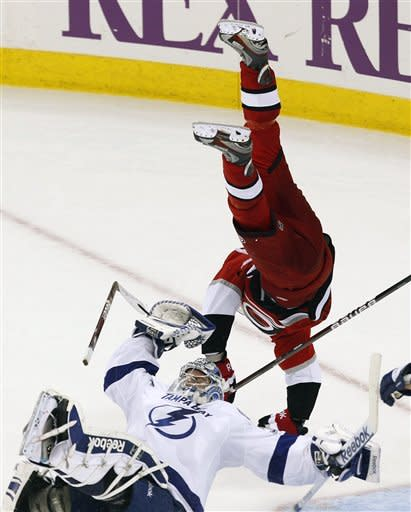 Carolina Hurricanes' Brandon Sutter (16) sails over the Tampa Bay Lightning's Mathieu Garon (32) during overtime in an NHL gamein Raleigh, N.C. on Saturday, March 3,  2012.  Sutter was called for a penalty on the play and the Lightning scored on the ensuing power play to win the game 3-2. (AP Photo/The News & Observer, Chris Seward) MANDATORY CREDIT