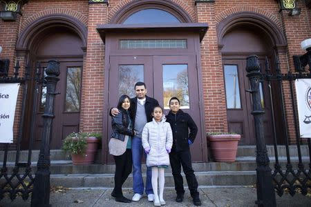 Angela Navarro, an undocumented Honduran-born immigrant with a deportation order, poses with her family - her husband Ermer and two U.S. born children, Angela, 8, and Arturo, 11, after moving into West Kensington Ministry Church with her family, in Philadelphia, Pennsylvania November 18, 2014. REUTERS/Mark Makela